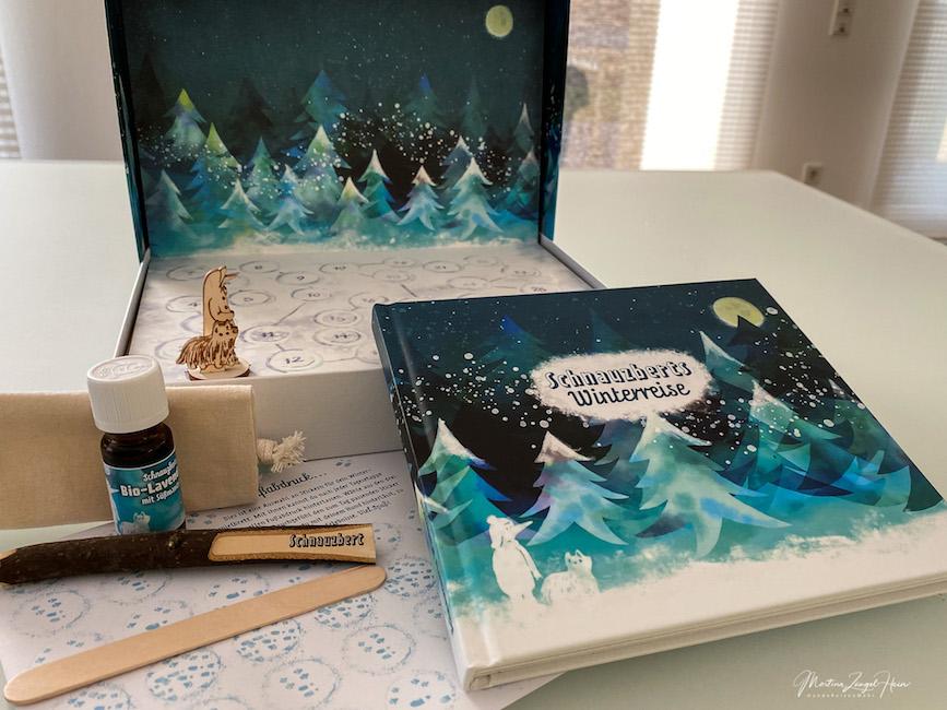 Das Winterrreise-Buch wird durch Spielbrett mit Spielfigur, Duftöl sowie Stift und Papieröffner ergänzt.